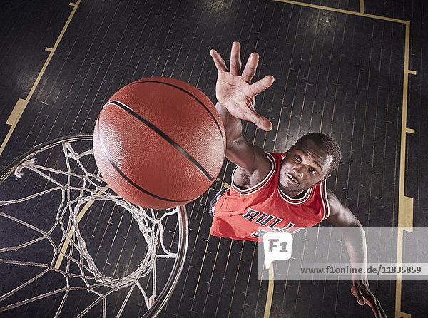Overhead-Ansicht junger männlicher Basketballspieler, der springt, um den Ball auf die Basketballfelge zu prallen.