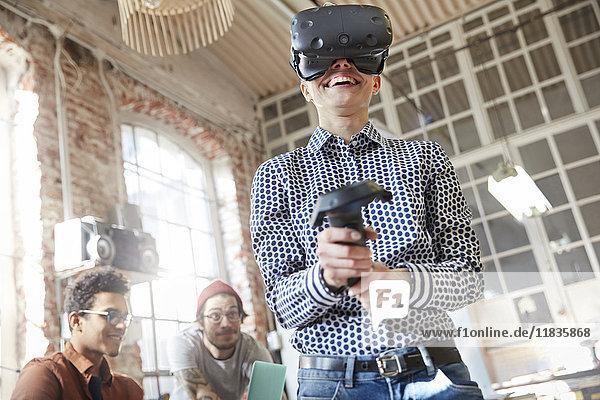 Lächelnde Programmiererin testet Virtual-Reality-Simulator-Brille und Joystick