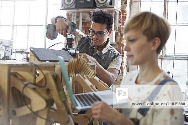 Konstrukteure mit Laptop und Bohrmaschine in der Werkstatt