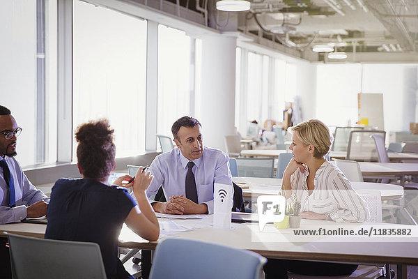 Geschäftsleute bei Tisch im gemeinsamen Arbeitsbereich