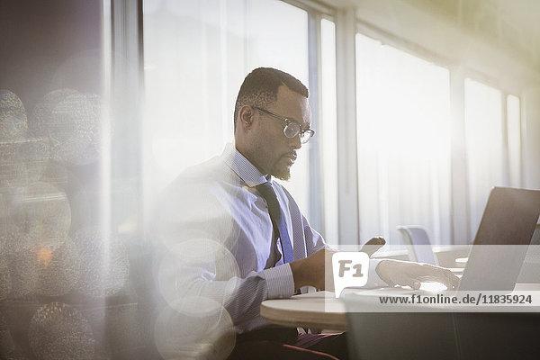 Serious Geschäftsmann SMS mit Handy am Laptop im Büro