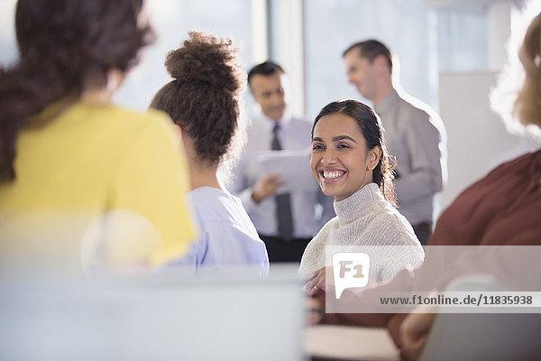 Lächelnde Geschäftsfrau im Gespräch mit Kollegen im Konferenzpublikum