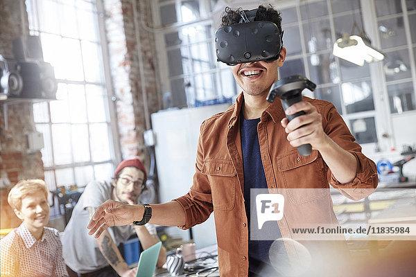 Lächelnder männlicher Programmierer  der in der Werkstatt Simulatorbrille und Joystick simuliert