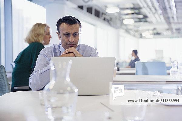 Fokussierter  seriöser Geschäftsmann  der am Laptop im Büro arbeitet.