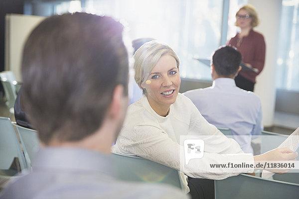 Lächelnde Geschäftsfrau im Gespräch mit Geschäftsmann im Konferenzpublikum