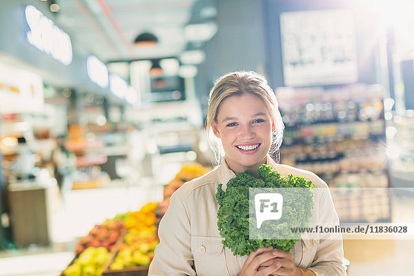 Portrait smiling young woman holding bunch of kale in grocery store market