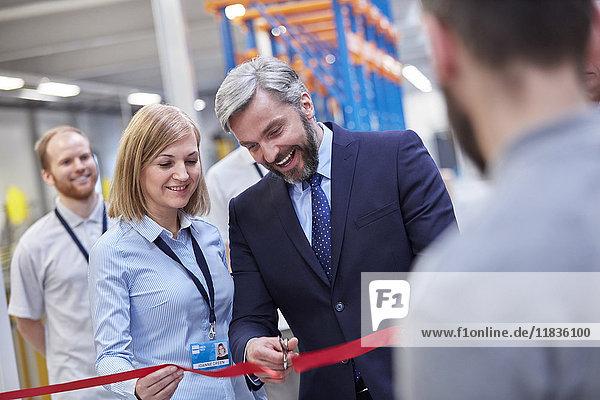 Geschäftsmann und Geschäftsfrau beim Durchtrennen des zeremoniellen Bandes in der Faseroptikfabrik