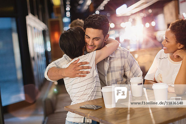 Young couple hugging  drinking coffee in cafe