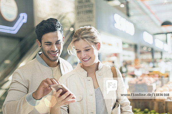 Smiling young couple using cell phone in grocery store market
