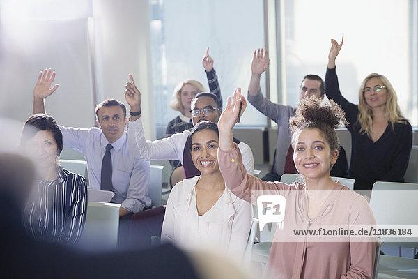 Lächelnde Geschäftsleute stellen eine Frage im Konferenzpublikum