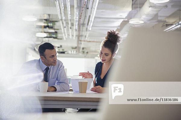 Geschäftsmann und Geschäftsfrau besprechen Papierkram im Büromeeting