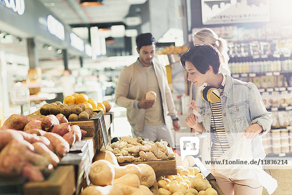 Young woman with headphones grocery shopping  browsing produce in market
