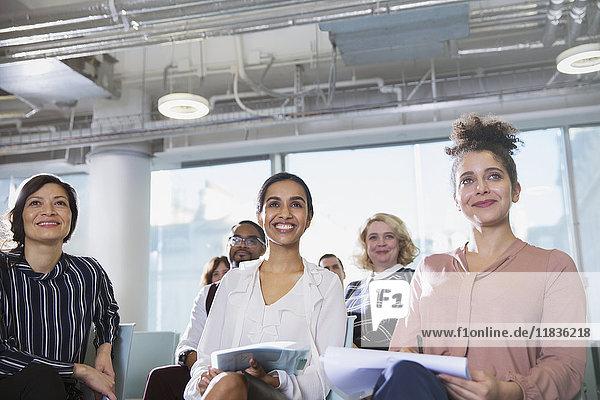 Lächelnde  aufmerksame Geschäftsfrau beim Zuhören im Konferenzpublikum