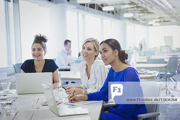Geschäftsfrauen an Laptops beim Zuhören im Büromeeting