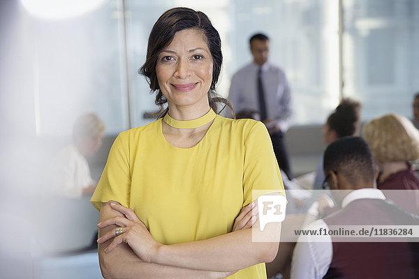 Portrait lächelnde  selbstbewusste Geschäftsfrau im Konferenzpublikum