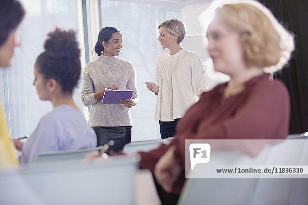 Geschäftsfrauen sprechen im Konferenzpublikum