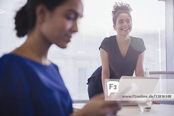 Lächelnde Geschäftsfrau lehnt sich an den Laptop im Konferenzraum Meeting