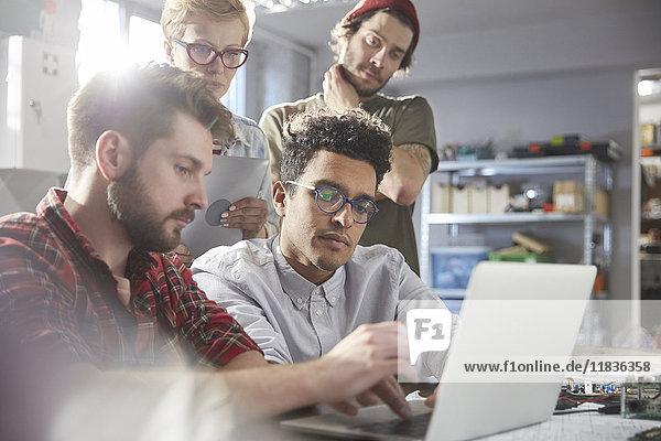 Seriöse, fokussierte Designer bei der Arbeit am Laptop in der Werkstatt