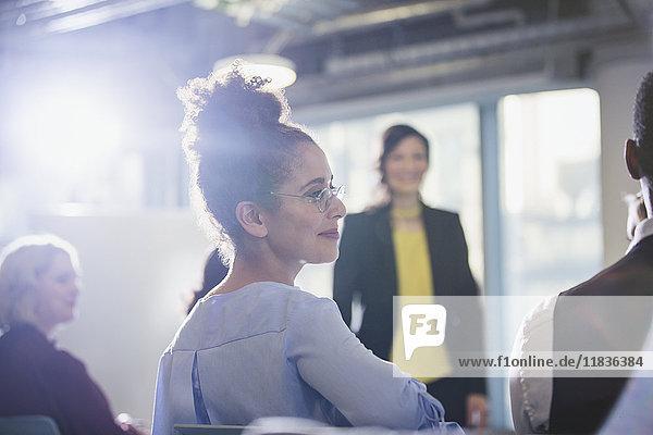 Geschäftsfrau beim Drehen  Zuhören im Konferenzpublikum