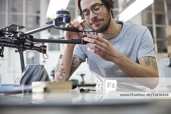 Männlicher Designer mit Tätowierungen und Drohne in der Werkstatt
