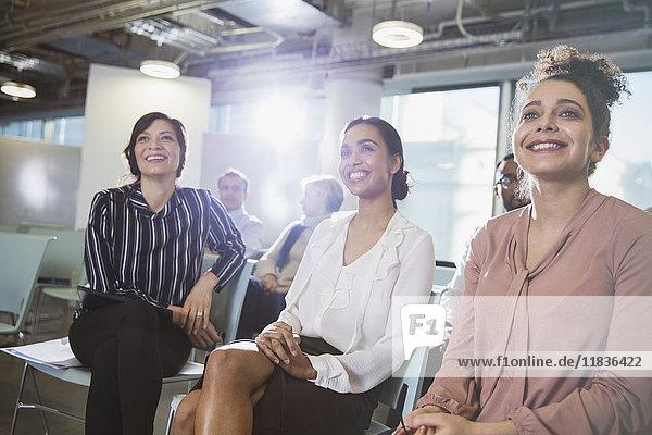 Lächelnde Geschäftsfrauen beim Zuhören im Meeting
