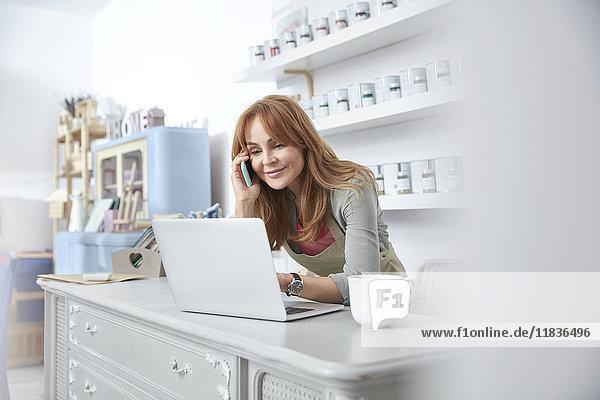 Lächelnde Geschäftsfrau mit Laptop und Handy an der Theke in der Kunstlackiererei