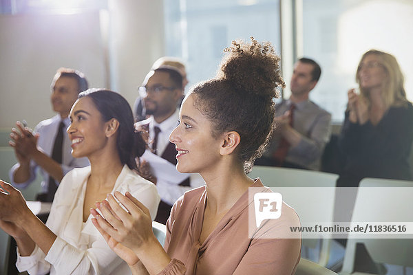 Businesswomen clapping in conference audience