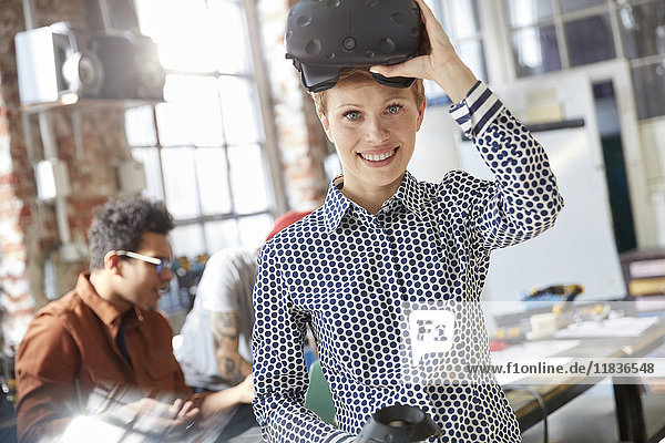 Portrait smiling female computer programmer wearing virtual reality simulator glasses