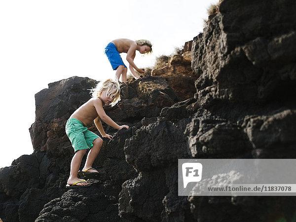 USA  Hawaii  Kauai  Boys (4-5  8-9) climbing on rocks