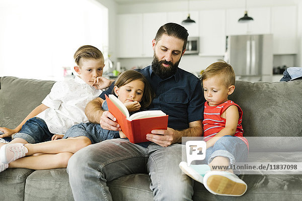 Father with his three children (2-3  6-7) reading book