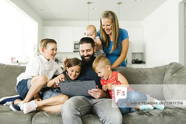Family with four children (6-11 months  2-3  6-7) using digital tablet