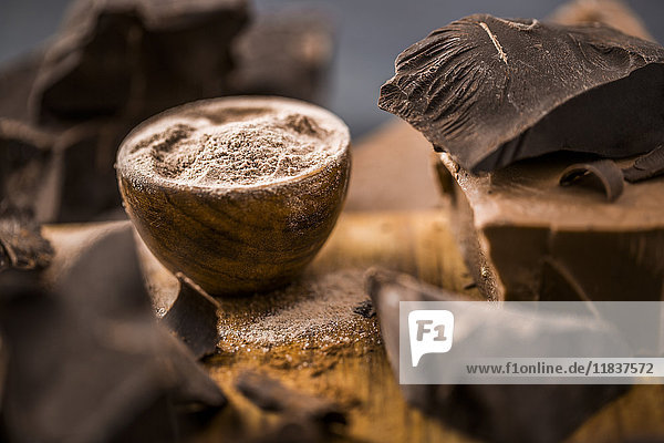 Ground chocolate in wooden bowl next to chunk of chocolate