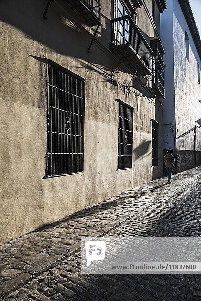 Spain  Andalusia  Granada  Woman walking along cobblestone street