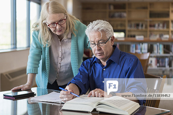 Older woman helping man reading book in library