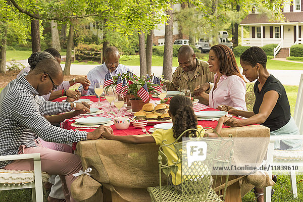 Multi-generation family praying at picnic table