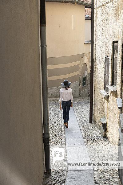 Woman wearing sun hat walking on narrow sidewalk