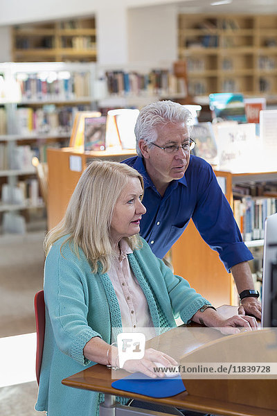 Older man helping woman using computer in library