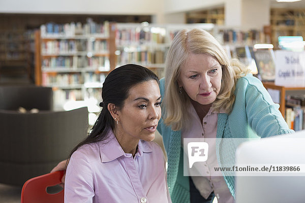 Older woman helping woman using computer in library