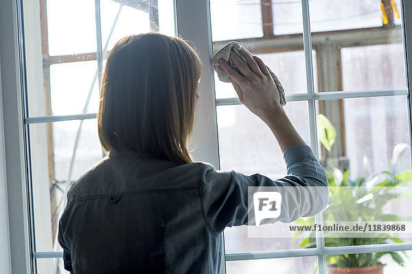Woman cleaning window with rag