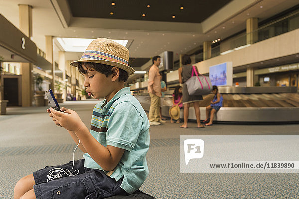Boy playing on cell phone in airport