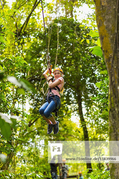 Caucasian girl hanging on zip line in forest
