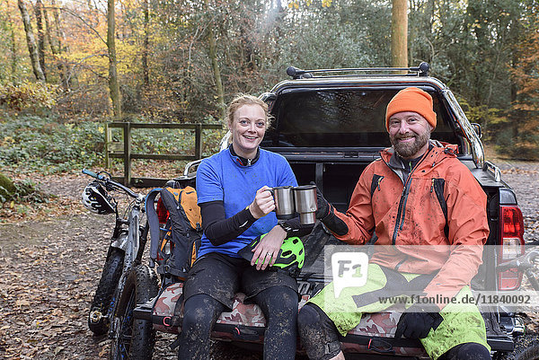 Caucasian couple toasting with coffee cups in pickup truck