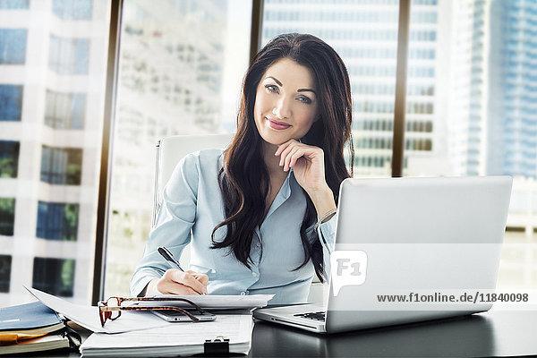 Caucasian businesswoman writing on paperwork
