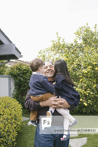 Boy and girl kissing grandfather