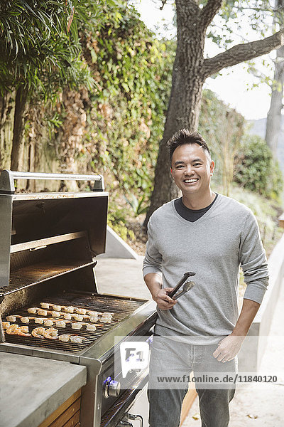 Portrait of smiling Chinese man cooking on grille