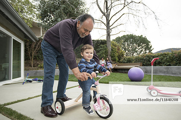 Grandfather pushing grandson on tricycle