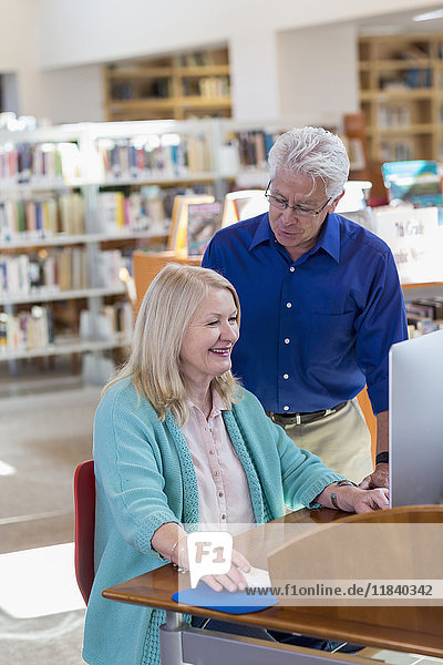 Older man watching woman using computer in library