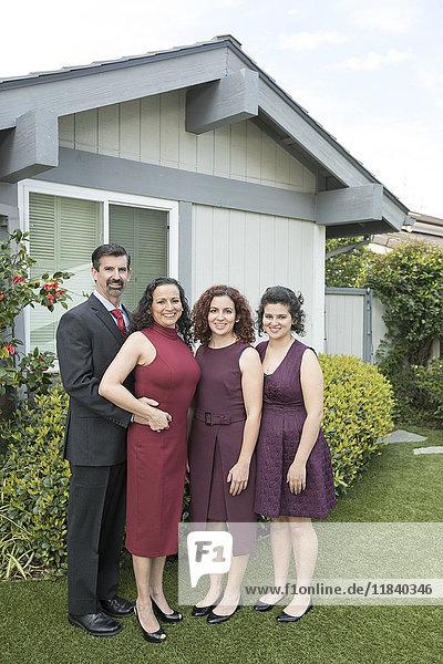 Family posing near house