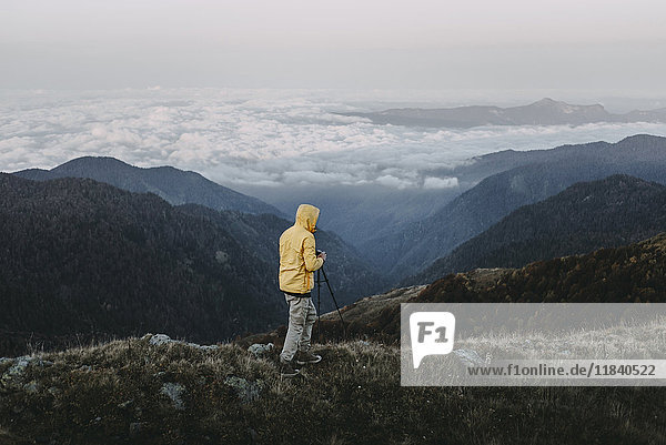 Caucasian man photographing in remote mountain landscape