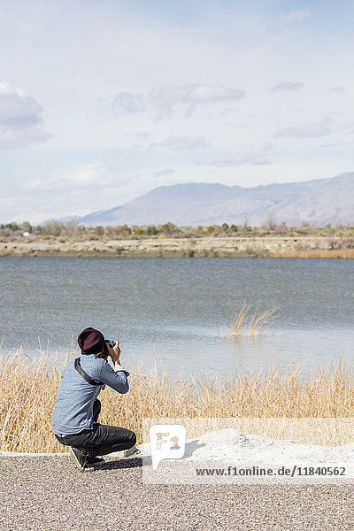 Caucasian woman photographing mountains at river
